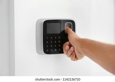 Mature man entering code on alarm system keypad indoors