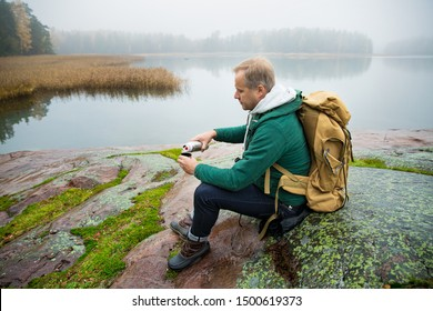 Mature man exploring Finland in the fall. Hiker with big backpack sit on mossy rock, drink hot coffee from thermos flask. Scandinavian landscape with misty sea and autumn forest.