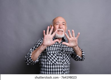 Mature man expressing disgust on face and making objection gesture with hands, grimacing on camera, gray studio background. Negative emotions, copy space