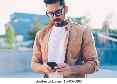 Mature man in eyewear for vision correction updating application on cellular phone while standing on urban setting and using public internet connection, Caucasian male blogger writing message