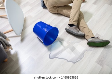 Mature Man Falling On Wet Floor In Front Spilled Bucket Of Water At Home