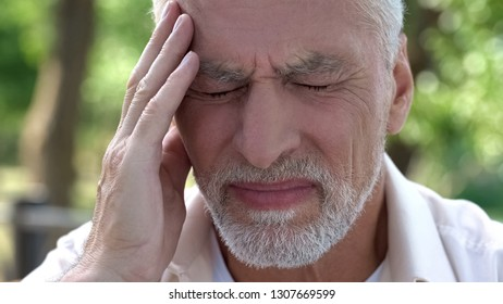 Mature man feeling sudden sharp pain in head, migraine attack, risk of thrombus