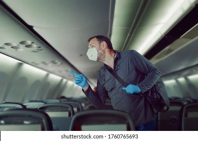 Mature man finds his seat on a plane. He wearing white face mask and blue rubber gloves