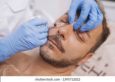 Mature man getting liquid rhinoplasty by professional cosmetologist. Attractive male client getting non-surgical nose job at cosmetology clinic. Beautician injecting filler in the face of mature man