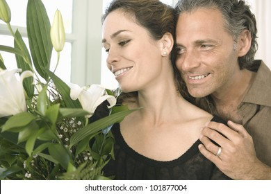 Mature man giving  a woman a bunch of flowers at home.