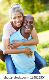 Mature Man Giving Woman Piggyback In Countryside