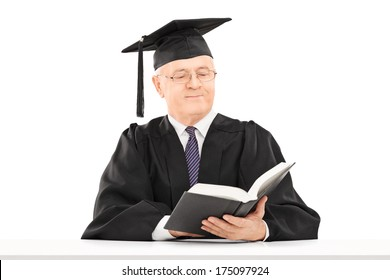 Mature man with graduation hat reading a book seated on table isolated on white background