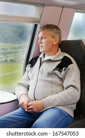 mature man in a gray cardigan sits in a car of a train and looks out of the window