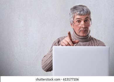 A mature man with gray hair wearing glasses siting at the table working with his laptop typing some documents looking with astonishment into camera pointing at you with his finger.