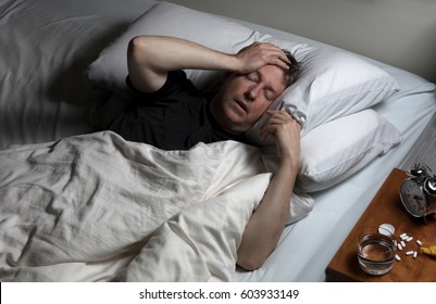 Mature man with hand on forehead while trying to sleep in bed. Insomnia concept with pain medicine on nightstand.
