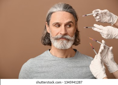 Mature man and hands holding syringes for anti-aging injections on color background