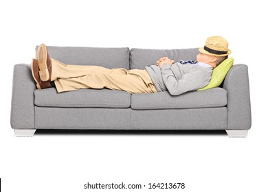Mature man with hat over his head sleeping on a sofa isolated on white background