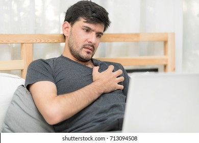 Mature Man Having worry for Suffering From Heart Pain While using laptop searching for Basic Help On Bedroom.Protecting Heart Attack. Acute Exacerbation Of Chronic Heart Failure Concept.