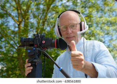 A mature man with headphones, using a camera dslr