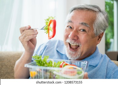 Mature man with healthy food, Portrait Asian Senior man eating a salad in house, Old elderly male health care eat vegetables and useful foods.