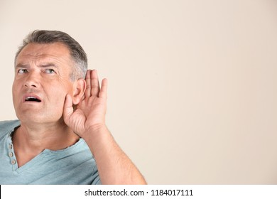 Mature man with hearing problem on light background. Space for text