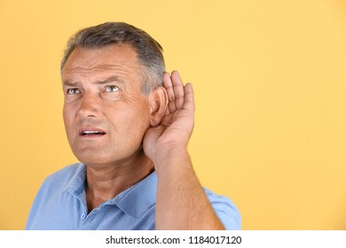 Mature man with hearing problem on color background. Space for text
