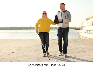 Mature man helping blind person with long cane in city