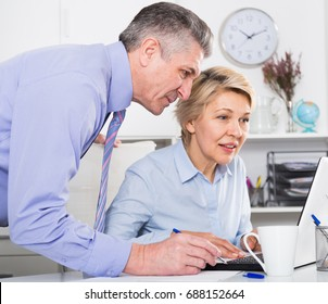 Mature man helping his colleague to make document and gives advice