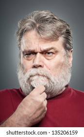A mature man in his 50's stroking his beard while making a decision.