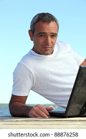A mature man with his laptop by the seashore.