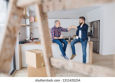 A mature man with his senior father furnishing new house, a new home concept.
