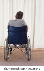 Mature man in his wheelchair with his back to the camera at home