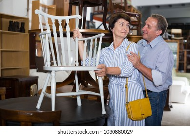 Mature man with his wife are buying armchair in antique store.