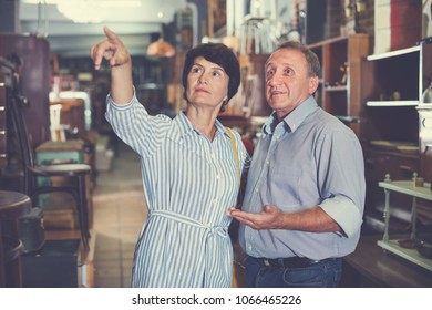 Mature man with his wife are choosing furniture at the antique shop. Focus on both persons