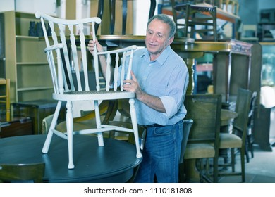 Mature man with his wife are choosing old chair at a antique shop. Focus on both persons