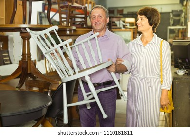 Mature man with his wife are choosing an old chair at antique shop. Focus on both persons