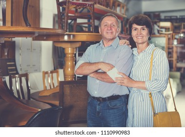 Mature man and his wife are choosing furniture in a antique shop. Focus on both persons