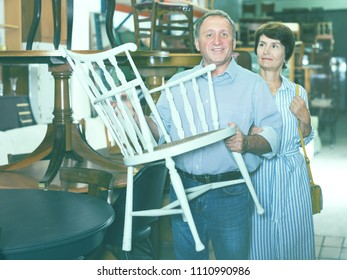 Mature man with his wife are choosing the old chair in antique shop. Focus on man