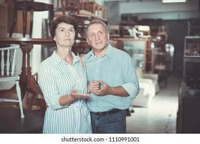 Mature man with his wife are choosing the furniture in the antique shop. Focus on both persons
