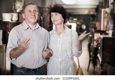 Mature man with his wife are choosing furniture in a antique shop. Focus on man
