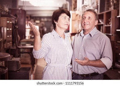 Mature man with his wife are choosing a furniture in the antique shop. Focus on both persons