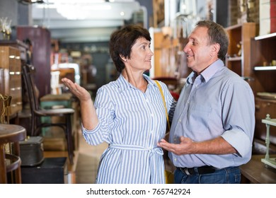 Mature man with his wife are choosing a furniture in a antique shop. Focus on both persons