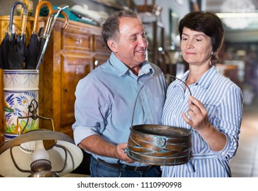 Mature man with his wife are satisfied of furniture at a antique shop. Focus on both persons