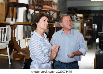 Mature man with his wife are shopping the old buffete in the antique store.