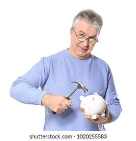 Mature man holding hammer over piggy bank on white background