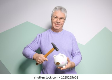Mature man holding hammer over piggy bank on color background
