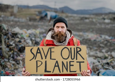Mature man holding placard poster on landfill, environmental pollution concept.