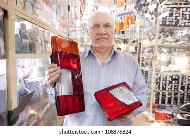 mature man holds  automotive  headlight  in  auto parts store