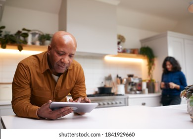 Mature Man At Home In Kitchen Looking At Digital Tablet With Female Partner In Background
