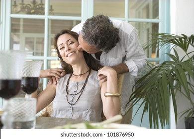 Mature man kissing woman while having a healthy lunch at home.