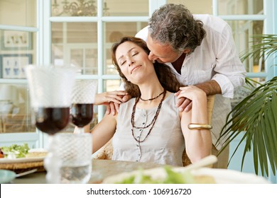 Mature man kissing woman while sitting at healthy lunch table, outdoors.