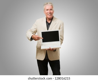 Mature Man With Laptop against a grey background