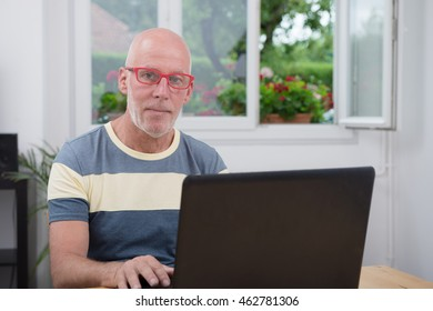 a mature man with laptop in his home