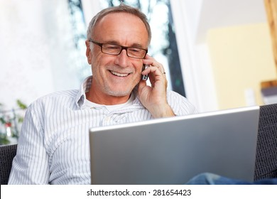 mature man with laptop mobile phone and reading specs, smiling