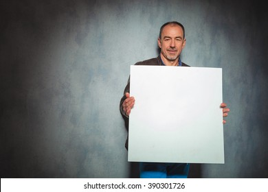 mature man in leather jacket holding blank board in gray studio background while looking at the camera